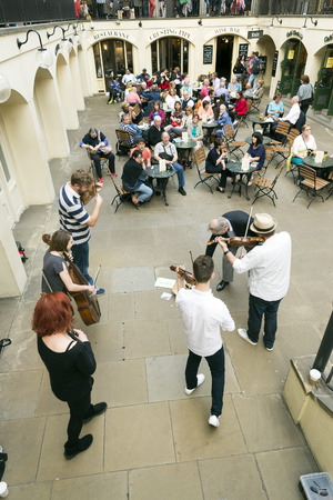 LONDON, UNITED KINGDOM - JUNE 5, 2014: Musicians performing at Covent Garden, London to entertain people in nearby restaurants and promote their CDs