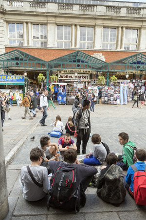 LONDON, UNITED KINGDOM - JUNE 5,  2014:  Crowds gather on a sunny spring day in Covent Garden as street entertainers perform in the paved area.