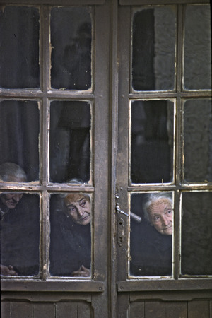 prying: Three old women seen through the window of his house, what happens on the street of a Castilian village on May, 1978, in Covarrubias, Spain