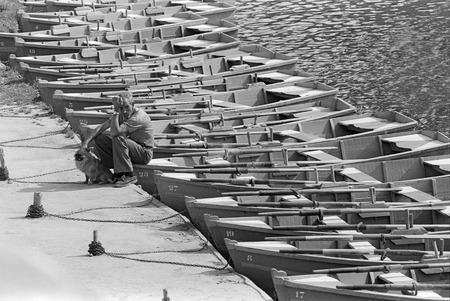 boatman: A boatman sits in a boat and playing with her dog, waiting for customers near the river Pisuerga on July, 1979 in Valladolid, Spain. Black and white