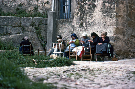 ar: A group of women of the village sew together at the front of a stone house on June, 1980 in Miranda del Castañar, Salamanca, Spain