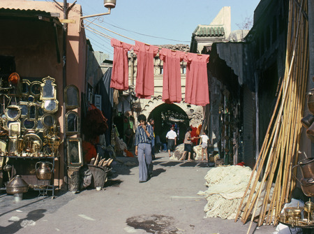 moorish clothing: MARRAKECH, MOROCCO – AUGUST, 1979: People walking down a shopping street in the medina of a North African city on August, 1979 in Marrakech, Morocco