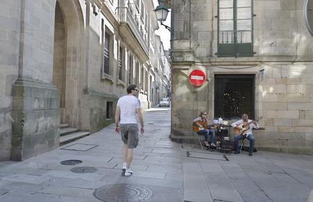 beggars: SANTIAGO DE COMPOSTELA, SPAIN – SEPTEMBER 8, 2012: Two street musicians play their guitars in a street in the historic center of Santiago de Compostela, Spain on September 8, 2012