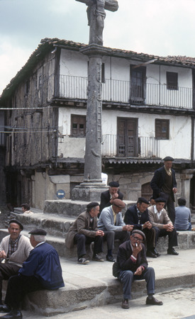 "seniority: A group of old men sitting on the steps of the ""rollo"" located in the main square of a medieval village of the Sierra de Francia on June, 1978 in La Alberca (Salamanca), Spain."