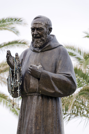 pio: LETOJANNI, SICILY, ITALY - SEPTEMBER 26, 2012: Bronze Statue of Padre Pio with rosaries. Saint Pio of Pietrelcina was a Capuchin Catholic priest from Italy who is venerated as a saint in the Catholic Church. On September 25, 2012 in Letojanni, Sicily, Ita