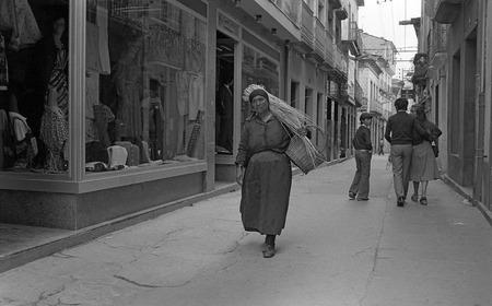 campesino: Una mujer campesina, vestida humildemente, que lleva una carga de paja sobre sus hombros lo largo de una calle de la ciudad. En blanco y negro