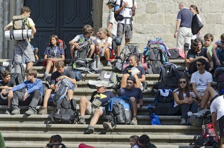 compostela: SANTIAGO DE COMPOSTELA, SPAIN SEPTEMBER 8, 2012: A group of young pilgrims end rest on the Camino de Santiago in the steps of Plateriass square, after reaching Santiago de Compostela, Spain on September 8, 2012