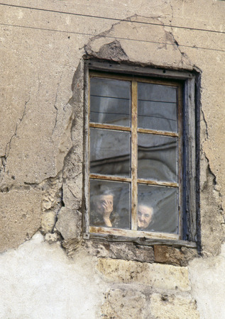 ruinous: Two elderly women seen through the window of his ruinous house, what happens on the street of a Castilian village on July, 1978, in Burgo de Osma, Soria, Spain Editorial