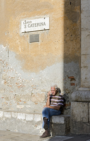 locality: Taormina, Sicily, Italy - September 27, 2012: An elder sat to the sun in the square of Saint Caterina, in the locality of Taormina, Sicily, Italy Editorial