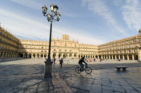 eventually: SALAMANCA, SPAIN - FEBRUARY 5, 2013: Cyclist and pedestrian. The Plaza Mayor of Salamanca, Spain, is an urban square built as Castilian that eventually became the center of social life of the city. On February 5, 2013