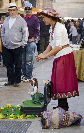 itinerant: TORO (ZAMORA), SPAIN - OCTOBER 13, 2012: A unidentified young woman with a little itinerant marionettes theater is entertaining the tourists that curiously is watching the show, at the grape harvest festival, on October, 13, 2012 in Toro (Zamora), Spain Editorial