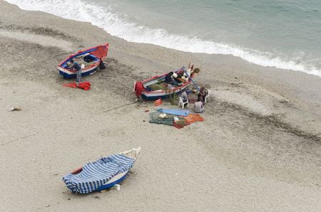 redes de pesca: NERJA, MALAGA PROVINCE, SPAIN - APRIL 17, 2013: Fishermen sewing fishing nets on the beach in Nerja, Malaga Province, Spain