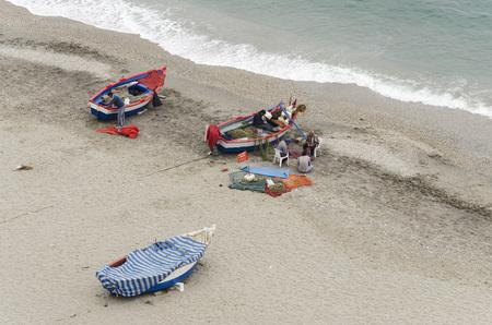 nerja: NERJA, MALAGA PROVINCE, SPAIN - APRIL 17, 2013: Fishermen sewing fishing nets on the beach in Nerja, Malaga Province, Spain