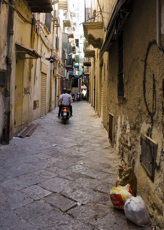 circulate: PALERMO, SICILY, ITALY - OCTOBER 3, 2012: Two unidentified men on a moped circulate through a narrow alley in which there are trash bags, on October 3, 2012 in Palermo, Italy