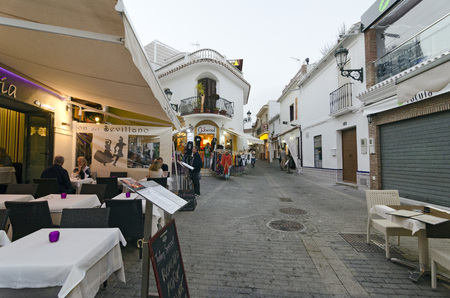 nerja: NERJA, MALAGA, SPAIN - APRIL 17, 2013:  People strolling at sunset along the pedestrian area full by entertainment facilities in Nerja, Malaga, Spain