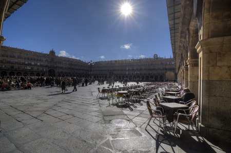 eventually: SALAMANCA, SPAIN - FEBRUARY 5, 2013: Cafe tables in Plaza Mayor. Salamanca. The Plaza Mayor of Salamanca, Spain, is an urban square built as Castilian that eventually became the center of social life of the city. On February 5, 2013