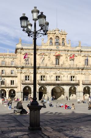 SALAMANCA, SPAIN - FEBRUARY 5, 2013: People sitting in the main square. The Plaza Mayor of Salamanca, Spain, is an urban square built as Castilian that eventually became the center of social life of the city. On February 5, 2013