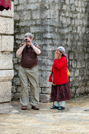 begs: KOTOR, MONTENEGRO - MAY 17, 2013: A gypsy woman begs to tourists on the streets of Kotor, Montenegro. On May 17, 2013 in Kotor, Montenegro