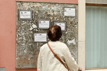 wastepaper basket: ZADAR, CROATIA - MAY 21, 2013: old woman standing reading the death notices which, in Croatia, are posted on public announcement boards. On May 21, 2013, in Zadar, Croatia Editorial