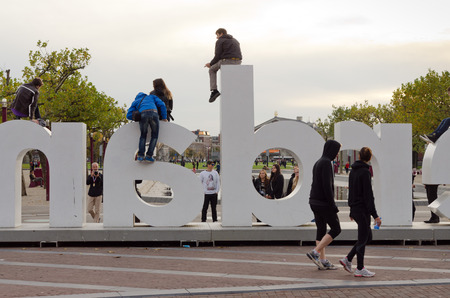 logo marketing: AMSTERDAM - OCTOBER 20, 2013: Young uploaded to letters of I Amsterdam logo at Museum Square on October 20, 2013. It is a city marketing initiative developed in 2005 as a means for Amsterdam to profile itself internationally.
