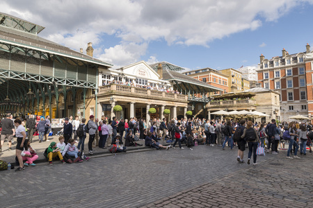 covent garden market: LONDON, UNITED KINGDOM - JUNE 5,  2014:  Crowds gather on a sunny spring day in Covent Garden as street entertainers perform in the paved area.