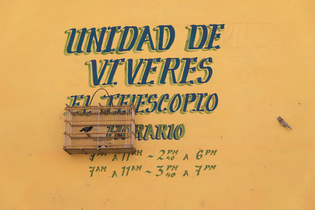 grocers: TRINIDAD, CUBA - MAY 8, 2014: Unidad de viveres. El Telescopio Notice of a grocery store painted on the wall next to a bird in a cage