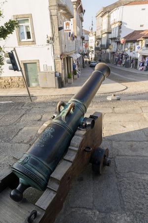 september 2: VALENÇA, PORTUGAL - SEPTEMBER 2, 2014: old cannon in a commercial street in the historic city center