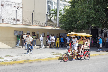 socialism: HAVANA , CUBA -  MAY 5, 2014 : People queue at the Spanish embassy to get a visa to leave Cuba, on May 5, 2014
