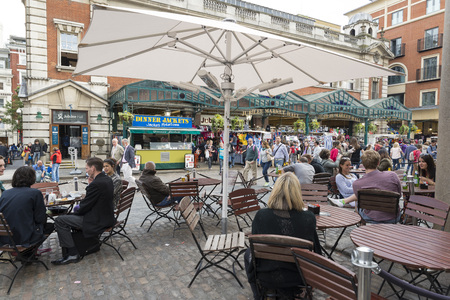 covent: LONDON, UNITED KINGDOM - JUNE 5,  2014: People having lunch at Covent Garden, London. The outer side offers small restaurants for hungry tourists and locals. People enjoy the sunshine under the parasols. Lively scene at one of Londons tourist hot-spots.