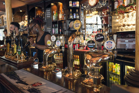 near beer: LONDON, UNITED KINGDOM - JUNE 5,  2014: A young waitress served beer in a pub near Covent Garden, London Editorial