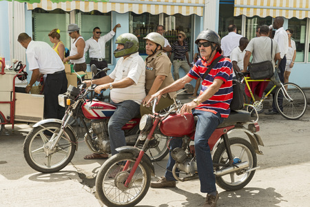 socialism: CIENFUEGOS, CUBA - MAY 7, 2014: Bikers on a downtown street. Motorbikes and bicycles are a popular form of transportation in Cuba