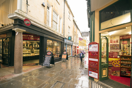 southgate: BATH, UK - JUNE 4, 014:Shoppers walk along a rain soaked street in the newly redeveloped Southgate commercial district.