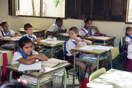 elementary age: HAVANA, CUBA - MAY 5, 2014: Group of Cuban schoolchildren of elementary age dressed in uniform sitting at a schoolhouse of Havana Editorial
