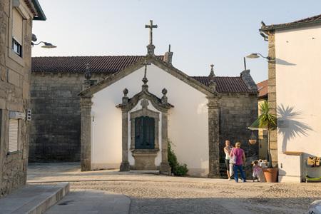 september 2: VALENÇA, PORTUGAL - SEPTEMBER 2, 2014: Two women with their children talk next to a church