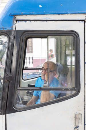 old bus: MATANZAS, CUBA - MAY 10, 2014:  An old bus driver waits for passengers in the main square of the colonial city of Matanzas Editorial