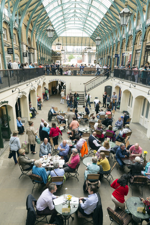 famous place: LONDON, UNITED KINGDOM - JUNE 5,  2014: Inside London Covent Garden marked, view from above at lunch time, people eating in multiple restaurants and cafe at this famous place. Editorial