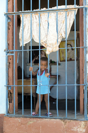 looking out: TRINIDAD, CUBA - MAY 8, 2014: Little boy looking out the window of his house