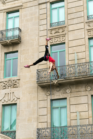 trapeze: PONTEVEDRA, SPAIN - SEPTEMBER 4, 2014: Acrobatic young woman hung from a rope during the Feira Franca a festival held annually