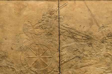 chariot: LONDON, UNITED KINGDOM - JUNE 5, 2014: British Museum. The King, Ashurbanipal, with his distinctive pointed hat, races though the arena in his chariot,
