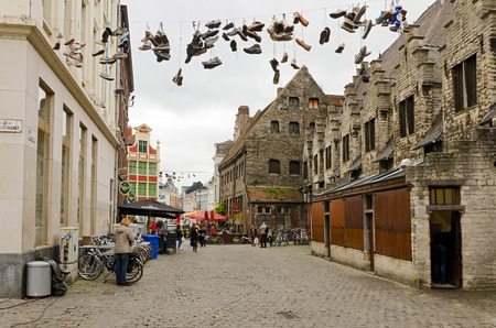 flemish: GHENT, BELGIUM - OCTOBER, 25: Multiple pairs of shoes flung over electric wire by shoelaces  on October 25, 2013, in Ghent, Belgium.  Ghent is a city and a municipality located in the Flemish region of Belgium.