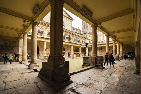 county somerset: BATH, UNITED KINGDOM - JUNE 4, 2014: A view of tourists walking around the main pool at the Roman Baths in Bath, England. With Bath Abbey in the background Editorial