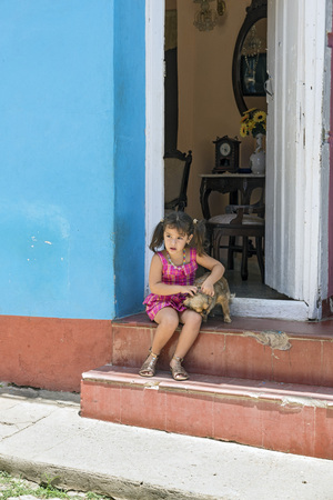cuba girl: TRINIDAD, CUBA - MAY 8, 2014: Little girl plays with her dog sitting at your doorstep Editorial