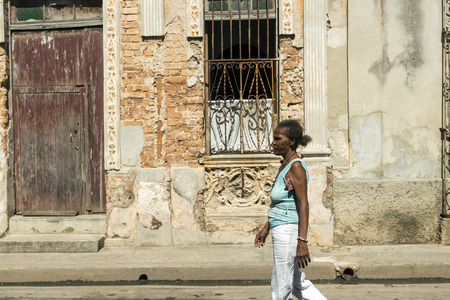 socialism: MATANZAS, CUBA - MAY 10, 2014: Mixed Elderly woman walks by a damaged downtown street in the city of Matanzas, Cuba