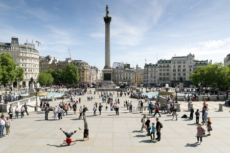 trafalgar: LONDON, UNITED KINGDOM - JUNE 6, 2014: Trafalgar Square, busy with people gathered all around. At its centre is Nelsons Column that commemorates the Battle of Trafalgar (1805), a British naval victory of the Napoleonic Wars.