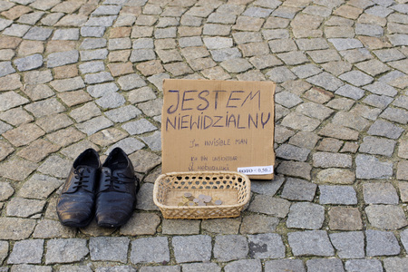 begs: WROCLAW, POLAND - OCTOBER24, 2014: An original form of begging: begs for money Invisible Man Editorial