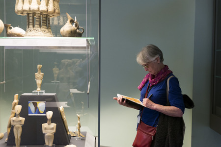 display case: LONDON, UNITED KINGDOM - JUNE 5, 2014: British Museum. A woman takes notes in a notebook of figurines in a display case.