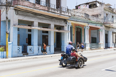 sidecar: HAVANA, CUBA - MAY 5, 2014: Two men on a motorcycle with sidecar driven on a street of Old Havana Editorial