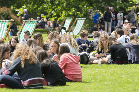 st jamess: LONDON, UNITED KINGDOM - JUNE 5, 2014: Young people talking and relaxing in St Jamess Park, during a warm Spring morning