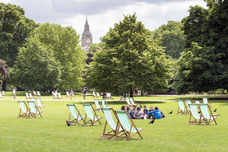 st jamess: LONDON, UNITED KINGDOM - JUNE 5, 2014: View of Big Ben from St. Jamess Park in London. Seated on the grass a youth group talks Editorial