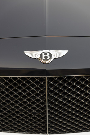 upper class: LIVERPOOL, ENGLAND - JUNE 8, 20149: Marque and grille of a Bentley Continental GT. A British manufacturer of prestige automobiles, the company was founded by Walter Owen Bentley in 1919 and has been owned by the Volkswagon Group since 1998. The business i Editorial